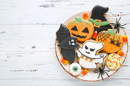 Halloween gingerbread cookies with candies and spiders on white wooden table Standard-Bild