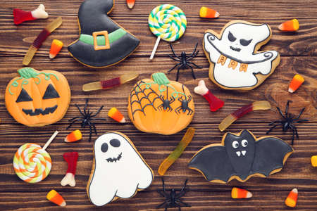 Halloween gingerbread cookies with candies and spiders on brown wooden table