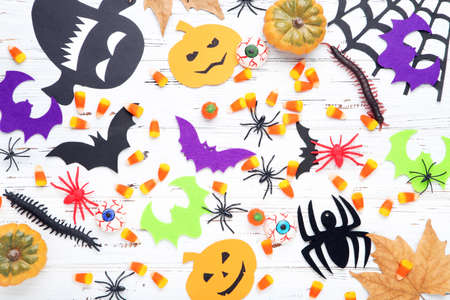 Halloween pumpkins, candies, paper ghosts, bats, spiders and maple leaf on wooden background