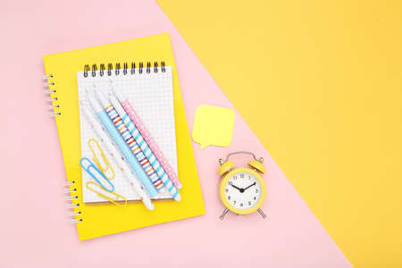School supplies with alarm clock on colorful background