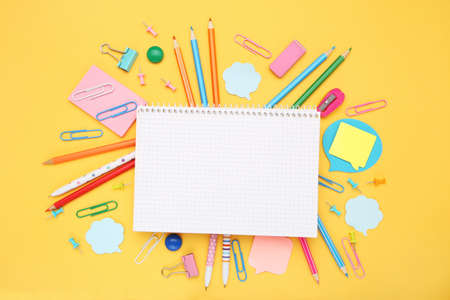 School supplies and notepad with space for text on yellow background
