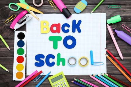 Different school supplies with text Back to School on wooden background