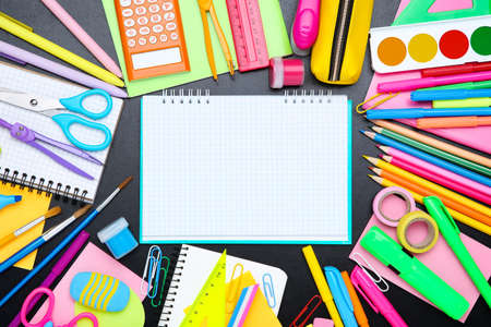 Different school supplies with blank sheet of paper on black background