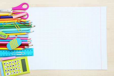 Blank sheet of paper with different school supplies on brown wooden table