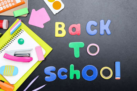 Different school supplies with text Back to School on black background
