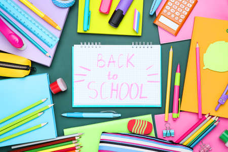 Different school supplies with text Back to School on green background Standard-Bild