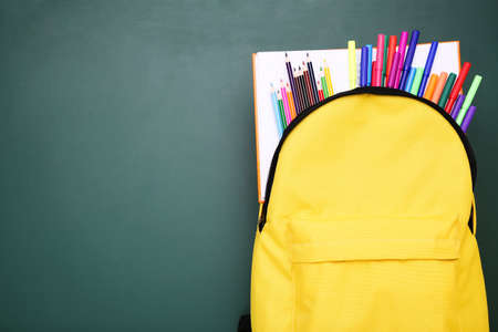 Backpack with school supplies on green background Standard-Bild