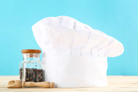 Chef hat with spices in jar and wooden scoop on blue background
