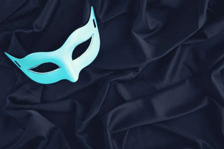 Carnival mask on black fabric background
