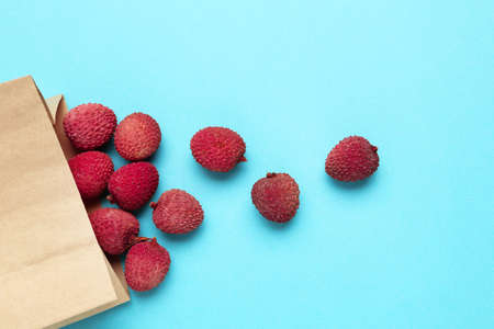 Tasty lychee in paper bag on blue background Standard-Bild
