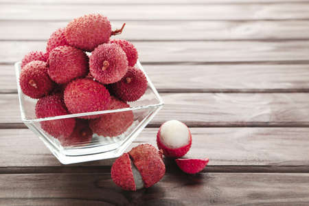 Tasty lychee in glass bowl on wooden table