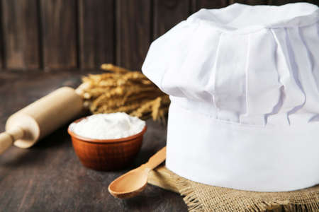 Chef hat with bowl of flour and rolling pin on wooden background