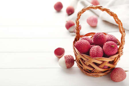 Tasty lychee in basket on white wooden table