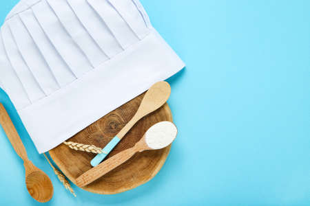 Chef hat with wooden spoons and flour on blue background