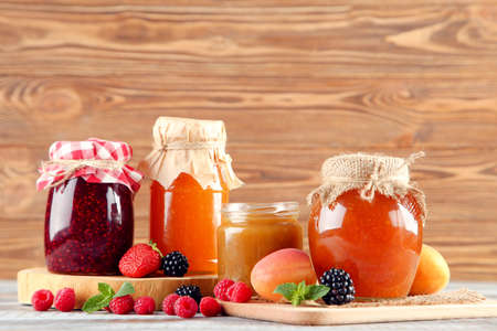 Sweet jam in glass jars with ripe berries on brown wooden table