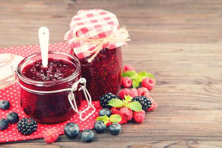 Sweet jam in glass jars with berries on wooden table Standard-Bild