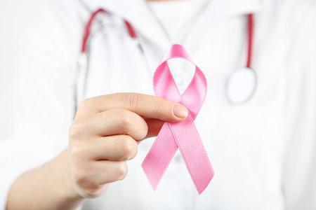 Breast cancer concept. Female hand holding pink ribbon Standard-Bild
