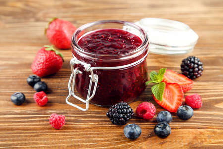Sweet jam in glass jar with ripe berries on brown wooden background Standard-Bild