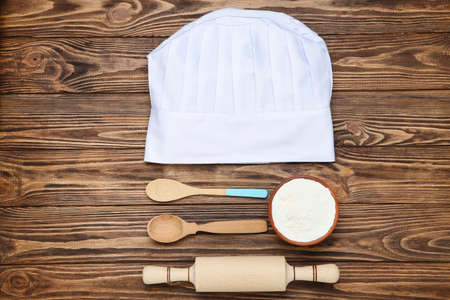 Chef hat with cooking cutlery and bowl of flour on wooden background