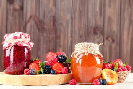 Jam in glass jars with fresh berries on wooden background Standard-Bild