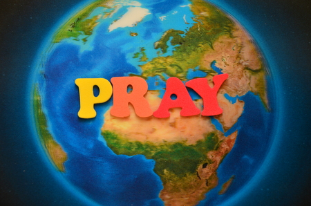 word pray on the world background