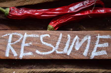 word resume on a wood plank with dry chillies on top