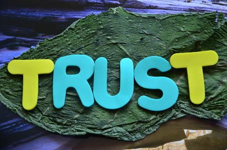 word trust on a green leaf background