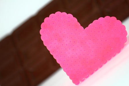 A pink heart of beading and milk chocolate Standard-Bild
