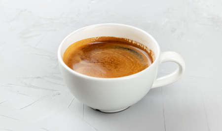 White cup of hot coffee americano on concrete background