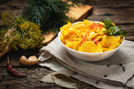 Vegan food - pickled cabbage with bell pepper on a wooden background, eco vegetables