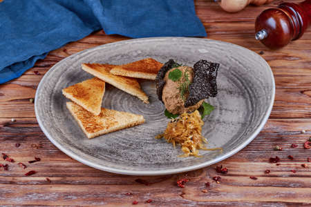 Liver pate with toast, wooden background