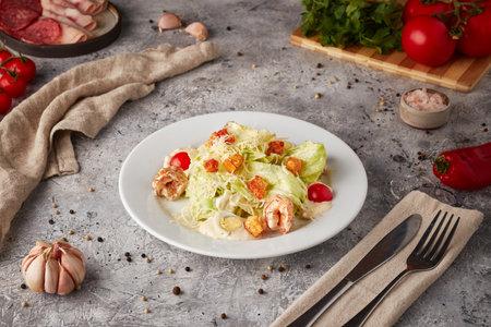 Caesar salad with shrimps, textured background