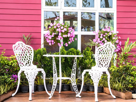 Vintage garden with white tea table and chairs photo