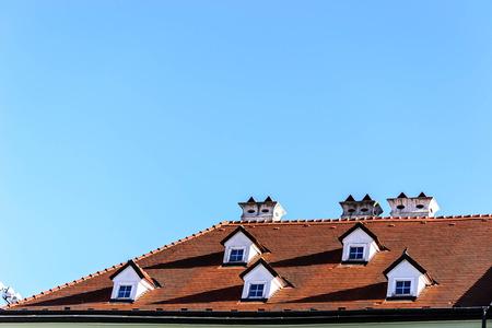 cedar shakes: Techo de tejas con ventanas del �tico en el cielo azul
