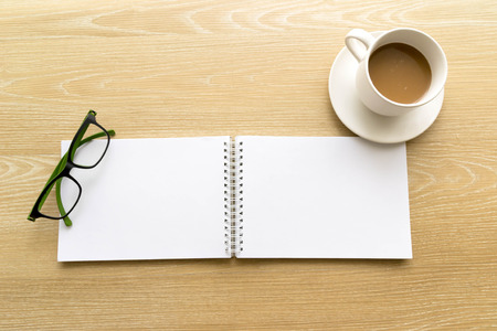 Time for creative. double blank paper with glasses and a cup of coffee on wood table photo