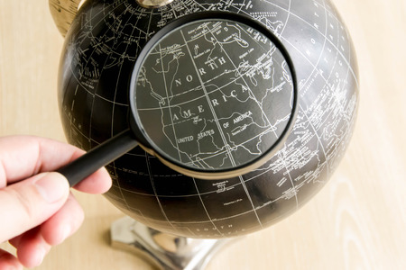 hand holding magnifying glass over the globe photo