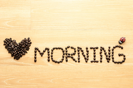 short phrase: coffee beans  used to spell love morning on wooden background Stock Photo