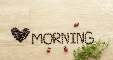 coffee beans  used to spell love morning on wooden background Stock Photo