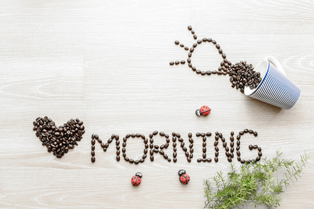 coffee beans  used to spell love morning on wooden background photo