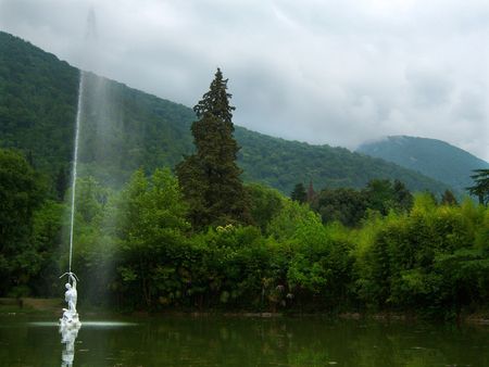 Pond with green water. In the center of the pond a fountain in the form of a man shooting from a bow upwards. A stream of water escapes from the arrow. The pond is arranged in an old overgrown park. Around the trees. In the background, mountains are overgrown with green forest. Above the mountains is a heavy sky in gray clouds. Around silence and peace. Calm, the warm summer rain will begin soon.