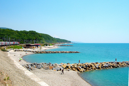 Summer. Blue sea. Blue sky. The sun is shining. The shore of the sea with breakwaters made of huge stones. Along the coast there is a railway on which the train is going. In the distance you can see the mountains.