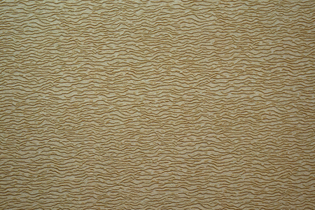 Paper dark beige with brown small spots relief in the form of waves, embossing, texture, background. Stock Photo