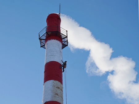 Industrial alpinism. Work at high altitude. The person performs the painting of the chimney. The pipe is red and white. From the pipe goes white smoke. Background clean blue sky.                                Stock Photo