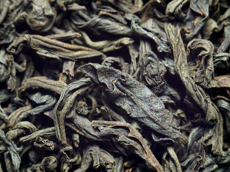 Background, texture. Dry leaves of black tea. Macro photo