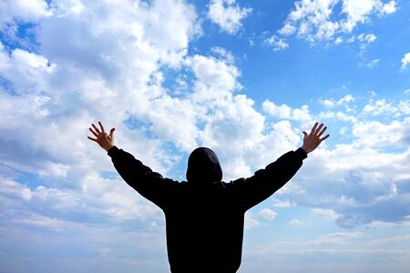 Feelings: freedom and flight. A hidden man in dark clothes and a hood feels free only in solitude with nature and the cloudy sky. A person wants to embrace the whole world and the sky.