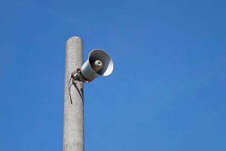 megaphone, horn on the concrete pillar against the blue sky