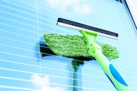 Washing the window with a special brush. Glass with sky reflection. Clean, cleaned. Jalousie.