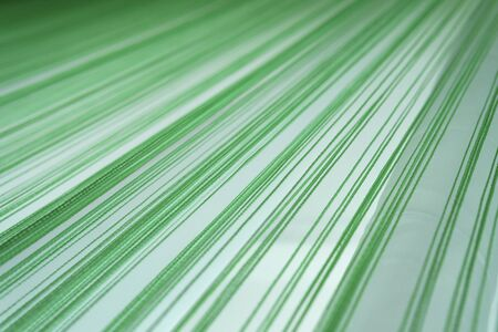 Background. Texture. Green threads on a white background go into the distance in perspective. The background is out of focus. Lots of parallel threads.