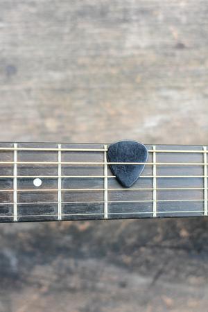 guitar pick: Guitar pick on finger board.