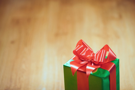 christmastime: Christmas presents with red ribbon on dark wooden background